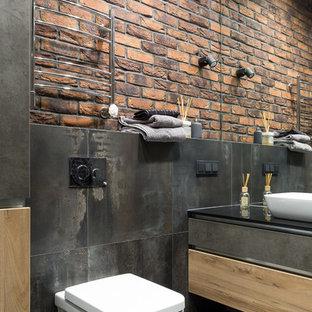 Создайте стильный интерьер: ванная комната среднего размера в современном стиле с плоскими фасадами, фасадами цвета дерева среднего тона, инсталляцией, черной плиткой, керамогранитной плиткой, полом из керамогранита, настольной раковиной, столешницей из искусственного камня, черным полом и черной столешницей - последний тренд