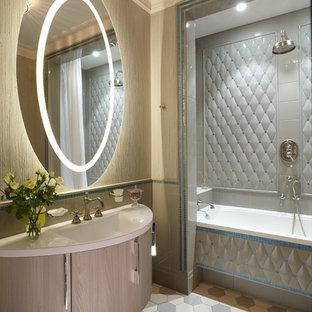 Новые идеи обустройства дома: ванная комната среднего размера в классическом стиле с плоскими фасадами, серой плиткой, бежевой плиткой, керамической плиткой, полом из керамической плитки, монолитной раковиной, светлыми деревянными фасадами, ванной в нише, душем над ванной, раздельным унитазом и бежевыми стенами