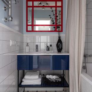 Пример оригинального дизайна: маленькая главная ванная комната в современном стиле с плоскими фасадами, синими фасадами, ванной в нише, душем над ванной, белой плиткой, синими стенами, монолитной раковиной, бежевым полом, шторкой для душа и белой столешницей