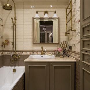 На фото: маленькие главные ванные комнаты в викторианском стиле с фасадами с утопленной филенкой, серыми фасадами, ванной в нише, душем над ванной, бежевой плиткой, серой плиткой и накладной раковиной