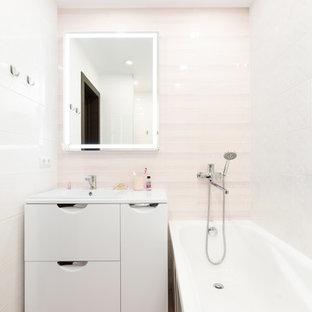 Modelo de cuarto de baño principal, contemporáneo, de tamaño medio, con armarios con paneles lisos, puertas de armario blancas, bañera encastrada sin remate, ducha abierta, sanitario de dos piezas, baldosas y/o azulejos rosa, baldosas y/o azulejos de cerámica, paredes rosas, suelo de baldosas de porcelana, lavabo bajoencimera, encimera de acrílico, suelo violeta, ducha abierta y encimeras blancas