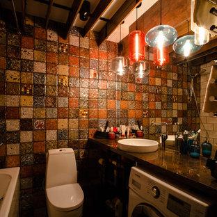Foto di una stanza da bagno padronale industriale di medie dimensioni con vasca ad alcova, vasca/doccia, WC monopezzo, piastrelle multicolore, piastrelle in ceramica, pareti multicolore, pavimento con piastrelle in ceramica, lavabo sottopiano e top in superficie solida