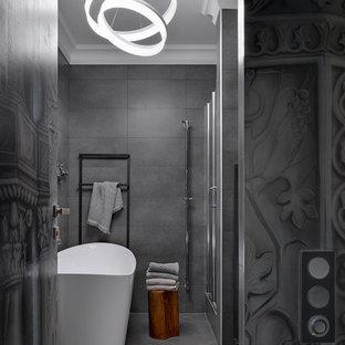 На фото: ванная комната в современном стиле с отдельно стоящей ванной, серой плиткой и серым полом с