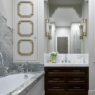 Стильный дизайн: главная ванная комната в стиле неоклассика (современная классика) с темными деревянными фасадами, полновстраиваемой ванной, серой плиткой, белыми стенами, врезной раковиной, серым полом, белой столешницей и мраморной плиткой - последний тренд