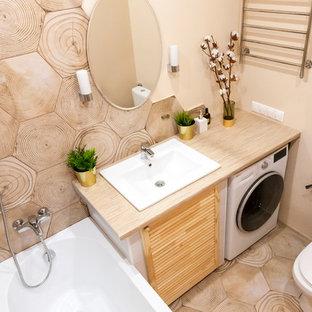 Стильный дизайн: маленькая главная ванная комната в скандинавском стиле с фасадами с филенкой типа жалюзи, фасадами цвета дерева среднего тона, полновстраиваемой ванной, душем над ванной, унитазом-моноблоком, коричневой плиткой, керамической плиткой, бежевыми стенами, полом из керамической плитки, врезной раковиной, столешницей из ламината, коричневым полом, шторкой для душа и бежевой столешницей - последний тренд