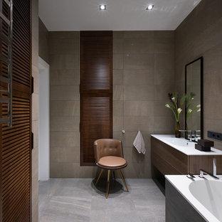 Свежая идея для дизайна: главная ванная комната в современном стиле с плоскими фасадами, темными деревянными фасадами, монолитной раковиной и серым полом - отличное фото интерьера