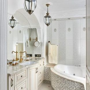 На фото: ванная комната в викторианском стиле с фасадами с выступающей филенкой, бежевыми фасадами, белыми стенами, врезной раковиной, гидромассажной ванной, белой плиткой и серой плиткой с