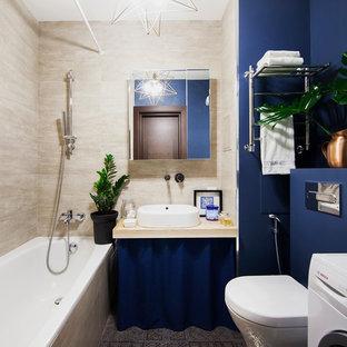 На фото: маленькая главная ванная комната в современном стиле с ванной в нише, душем над ванной, инсталляцией, бежевой плиткой, синими стенами, настольной раковиной, серым полом и шторкой для душа с