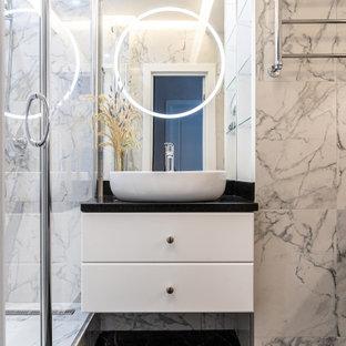 Пример оригинального дизайна: ванная комната среднего размера в современном стиле с плоскими фасадами, белыми фасадами, душем в нише, серой плиткой, душевой кабиной, настольной раковиной, черным полом, душем с распашными дверями, черной столешницей, тумбой под одну раковину и подвесной тумбой