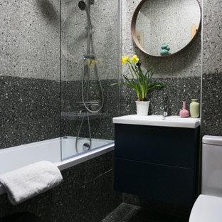Immagine di una piccola stanza da bagno padronale scandinava con ante lisce, ante blu, vasca sottopiano, vasca/doccia, WC monopezzo, piastrelle grigie, piastrelle in gres porcellanato, pareti grigie, pavimento in gres porcellanato, lavabo sospeso, top in superficie solida, pavimento grigio, doccia aperta, top bianco, un lavabo e mobile bagno sospeso