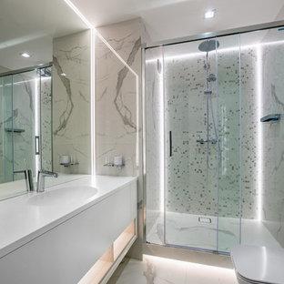 Стильный дизайн: ванная комната в современном стиле с плоскими фасадами, белыми фасадами, душем в нише, белой плиткой, душевой кабиной, монолитной раковиной, белым полом и белой столешницей - последний тренд