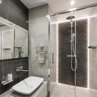 Источник вдохновения для домашнего уюта: серо-белая ванная комната в современном стиле с плоскими фасадами, серыми фасадами, душем в нише, серой плиткой, черной плиткой, душевой кабиной, настольной раковиной, серым полом и серой столешницей