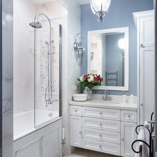 Стильный дизайн: главная ванная комната в стиле современная классика с фасадами с утопленной филенкой, белыми фасадами, ванной в нише, душем над ванной, синей плиткой, синими стенами, врезной раковиной и белым полом - последний тренд