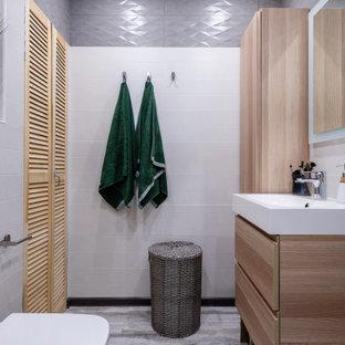 Стильный дизайн: маленькая ванная комната в скандинавском стиле с инсталляцией, плоскими фасадами, светлыми деревянными фасадами, белой плиткой, серой плиткой и серым полом - последний тренд