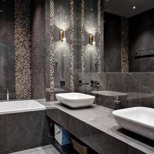 На фото: главная ванная комната в стиле неоклассика (современная классика) с серой плиткой, настольной раковиной, серым полом, ванной в нише и серой столешницей