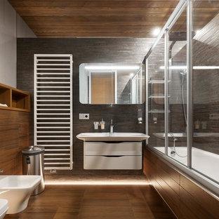Новые идеи обустройства дома: большая главная ванная комната в современном стиле с плоскими фасадами, белыми фасадами, ванной в нише, душем над ванной, биде, серой плиткой, монолитной раковиной, коричневым полом и душем с раздвижными дверями