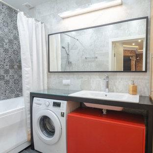 Modelo de cuarto de baño principal, industrial, pequeño, con armarios con paneles lisos, puertas de armario de madera oscura, bañera empotrada, baldosas y/o azulejos grises, baldosas y/o azulejos de piedra, paredes grises, suelo de baldosas de porcelana, lavabo bajoencimera y suelo gris