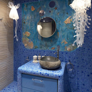 Inspiration for a large beach style master bathroom in Moscow with flat-panel cabinets, blue cabinets, a hot tub, a shower/bathtub combo, a wall-mount toilet, blue tile, mosaic tile, blue walls, ceramic floors, a vessel sink and tile benchtops.