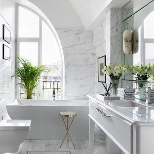 На фото: ванные комнаты в стиле современная классика с фасадами островного типа, белыми фасадами, отдельно стоящей ванной, белой плиткой, белыми стенами, врезной раковиной, белым полом и белой столешницей