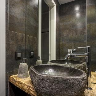 Идея дизайна: ванная комната в современном стиле с серой плиткой, настольной раковиной, столешницей из дерева и коричневой столешницей