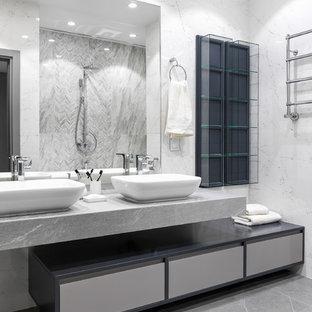 Пример оригинального дизайна интерьера: ванная комната в современном стиле с плоскими фасадами, серыми фасадами, белой плиткой, настольной раковиной, серым полом и серой столешницей