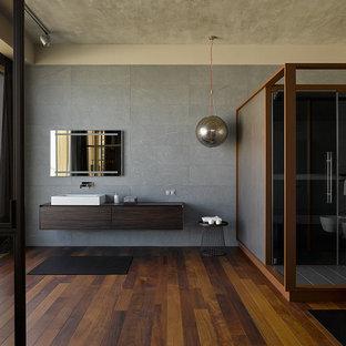 На фото: огромная ванная комната в современном стиле с плоскими фасадами, темными деревянными фасадами, серой плиткой, душевой кабиной, настольной раковиной, коричневым полом, серыми стенами, темным паркетным полом и душем с распашными дверями