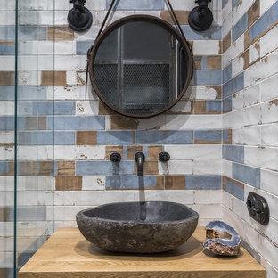 Новый формат декора квартиры: ванная комната в стиле лофт с плоскими фасадами, фасадами цвета дерева среднего тона, разноцветной плиткой, душевой кабиной, настольной раковиной, столешницей из дерева и коричневой столешницей