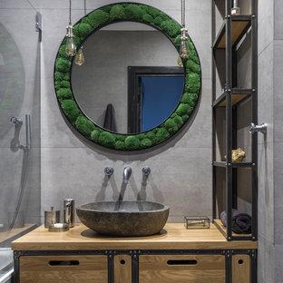 Imagen de cuarto de baño principal, urbano, con armarios con paneles lisos, puertas de armario de madera oscura, baldosas y/o azulejos grises, lavabo sobreencimera, encimera de madera y encimeras marrones