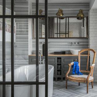 Пример оригинального дизайна: главная ванная комната в стиле современная классика с серыми фасадами, отдельно стоящей ванной, настольной раковиной, серым полом и коричневой столешницей