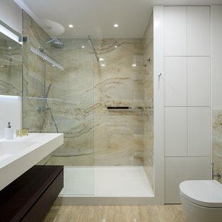 На фото: с высоким бюджетом ванные комнаты среднего размера в современном стиле с плоскими фасадами, бежевой плиткой, керамогранитной плиткой, белыми стенами, полом из травертина, душевой кабиной, столешницей из искусственного камня, бежевым полом, открытым душем, белой столешницей, темными деревянными фасадами, душем в нише, раздельным унитазом и монолитной раковиной