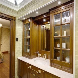 На фото: ванная комната в классическом стиле с фасадами цвета дерева среднего тона, бежевой плиткой, врезной раковиной и стеклянными фасадами с