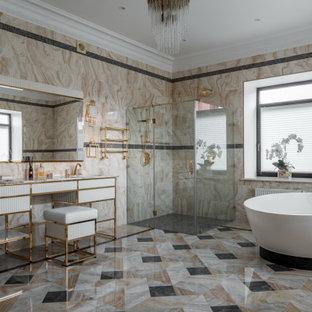 На фото: главная ванная комната в современном стиле с плоскими фасадами, белыми фасадами, отдельно стоящей ванной, угловым душем, бежевой плиткой, врезной раковиной, разноцветным полом и белой столешницей с
