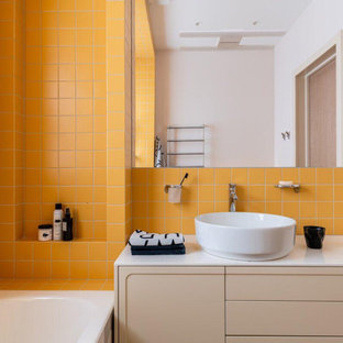 На фото: ванная комната в современном стиле с плоскими фасадами, бежевыми фасадами, оранжевой плиткой, настольной раковиной, белой столешницей, тумбой под одну раковину и встроенной тумбой