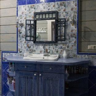 Diseño de cuarto de baño principal, de estilo de casa de campo, de tamaño medio, con armarios con paneles con relieve, puertas de armario de madera oscura, bañera exenta, combinación de ducha y bañera, sanitario de una pieza, baldosas y/o azulejos multicolor, baldosas y/o azulejos de cerámica, paredes azules, suelo de baldosas de porcelana, lavabo encastrado y encimera de acrílico