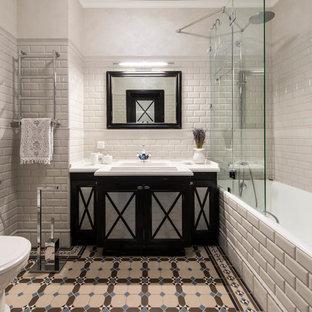 На фото: главные ванные комнаты в стиле современная классика с черными фасадами, ванной в нише, душем над ванной, раздельным унитазом, бежевой плиткой, накладной раковиной и разноцветным полом