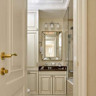 На фото: главная ванная комната в классическом стиле с фасадами с выступающей филенкой, белыми фасадами, ванной в нише, бежевыми стенами и разноцветным полом