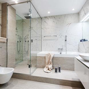 Выдающиеся фото от архитекторов и дизайнеров интерьера: главная ванная комната среднего размера в современном стиле с угловым душем, биде, серой плиткой, керамогранитной плиткой, полом из керамогранита, настольной раковиной, плоскими фасадами, бежевыми фасадами, накладной ванной, бежевым полом и душем с распашными дверями