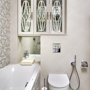 На фото: главная ванная комната в стиле неоклассика (современная классика) с ванной в нише, инсталляцией, серой плиткой, бежевой плиткой, бежевым полом и гигиеническим душем