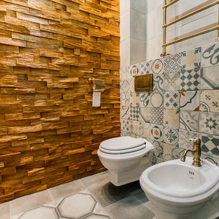 Inspiration for a mid-sized mediterranean 3/4 gray tile and porcelain tile porcelain floor and gray floor bathroom remodel in Other with a wall-mount toilet, gray walls, a vessel sink and wood countertops
