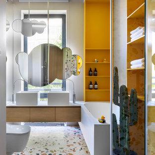 Пример оригинального дизайна: ванная комната в современном стиле с плоскими фасадами, фасадами цвета дерева среднего тона, угловой ванной, белыми стенами, полом из терраццо, настольной раковиной, разноцветным полом и белой столешницей