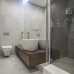 Свежая идея для дизайна: ванная комната в современном стиле с плоскими фасадами, темными деревянными фасадами, душем в нише, унитазом-моноблоком, серой плиткой, белой плиткой, душевой кабиной, настольной раковиной, столешницей из дерева, серым полом, душем с распашными дверями и коричневой столешницей - отличное фото интерьера