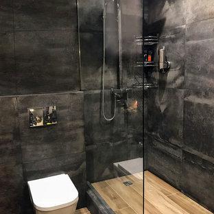 Идея дизайна: маленькая ванная комната в стиле лофт с инсталляцией, черной плиткой, черными стенами, душевой кабиной, столешницей из дерева, фасадами цвета дерева среднего тона, угловым душем, настольной раковиной, плоскими фасадами, керамогранитной плиткой, полом из плитки под дерево, коричневым полом, шторкой для ванной, коричневой столешницей, тумбой под одну раковину и подвесной тумбой