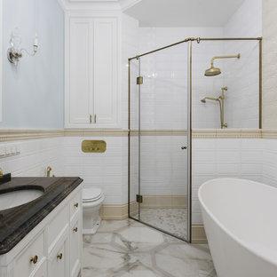 На фото: главная ванная комната в классическом стиле с фасадами с утопленной филенкой, белыми фасадами, отдельно стоящей ванной, угловым душем, раздельным унитазом, белой плиткой, синими стенами, врезной раковиной, бежевым полом, душем с распашными дверями и коричневой столешницей с