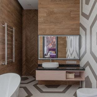 На фото: главные ванные комнаты в современном стиле с плоскими фасадами, отдельно стоящей ванной, разноцветным полом и черной столешницей