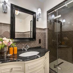 Удачное сочетание для дизайна помещения: ванная комната среднего размера в классическом стиле с бежевыми фасадами, коричневой плиткой, керамической плиткой, полом из керамогранита, душевой кабиной, мраморной столешницей, белым полом, душем с распашными дверями, душем в нише, врезной раковиной и черной столешницей - самое интересное для вас