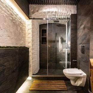 Ejemplo de cuarto de baño actual con armarios con paneles lisos, puertas de armario de madera oscura, ducha empotrada, sanitario de pared, paredes blancas, suelo negro, ducha con puerta corredera y encimeras marrones