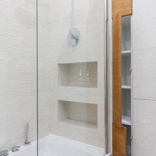 На фото: маленькие главные ванные комнаты в современном стиле с плоскими фасадами, фасадами цвета дерева среднего тона, душем над ванной, бежевой плиткой, керамогранитной плиткой и ванной в нише