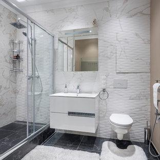 Новый формат декора квартиры: ванная комната в современном стиле с плоскими фасадами, белыми фасадами, душем в нише, инсталляцией, бежевой плиткой, белой плиткой, бежевыми стенами, душевой кабиной, монолитной раковиной, черным полом и душем с раздвижными дверями