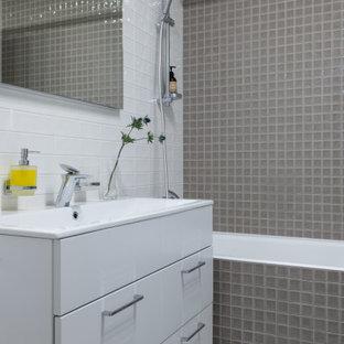 На фото: ванная комната в современном стиле с плоскими фасадами, белыми фасадами, ванной в нише, душем над ванной, серой плиткой, плиткой мозаикой, консольной раковиной, белым полом и шторкой для душа с