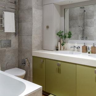 Foto di una stanza da bagno padronale design con ante lisce, ante verdi, vasca da incasso, WC sospeso, piastrelle grigie, pareti grigie e lavabo sottopiano